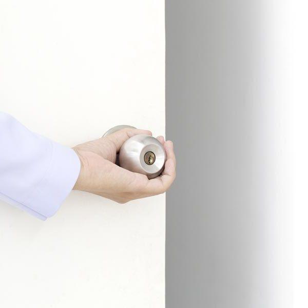 hand opening a white door with silver door knob