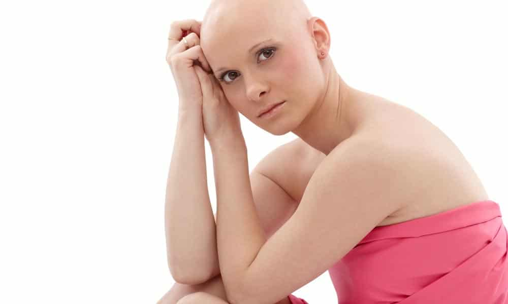 young bald woman after chemotherapy in a pink dress