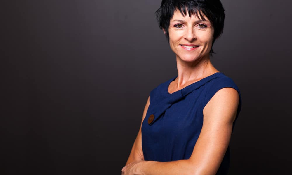 confident middle aged woman with black hair and blue dress