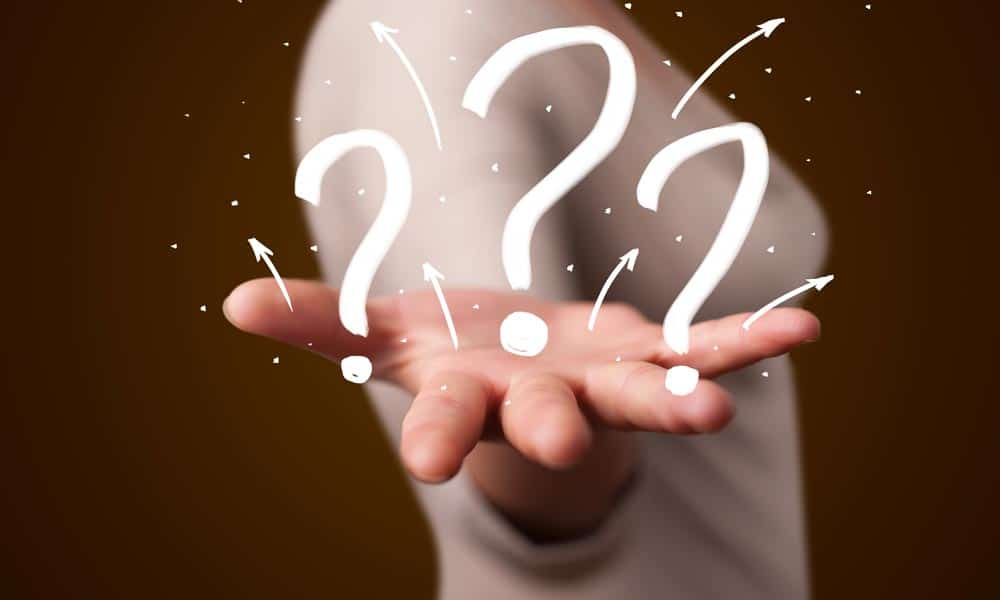 woman holding out her right hand with question marks on top