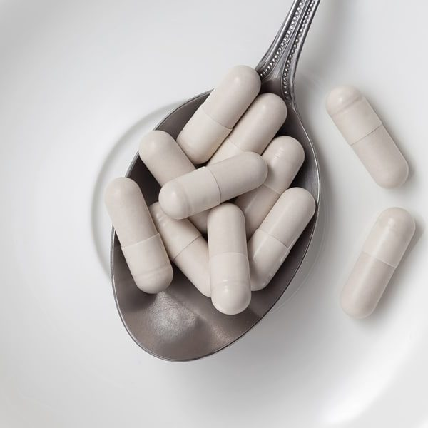 white vitamin capsules on a spoon